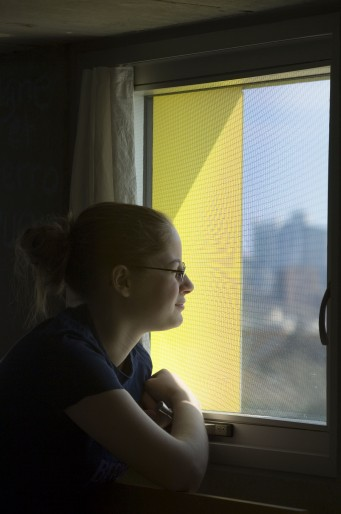 Student looking out Simmons Hall window