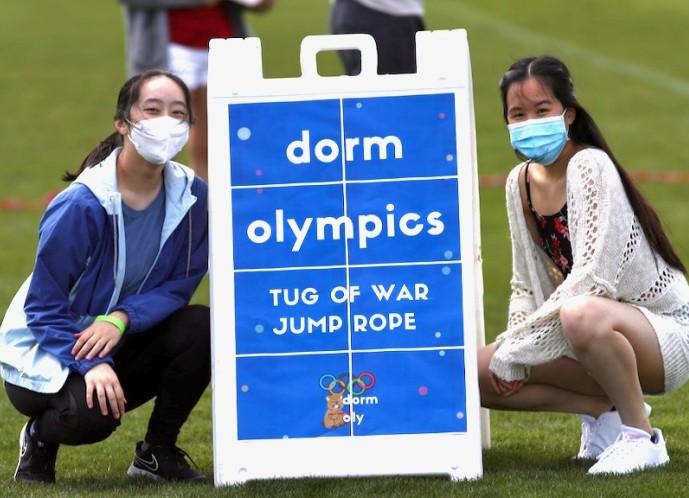 Ellie Feng (left and Ashley Ke (right) pictured with blue sign that reads dorm olympics tud og war jumprope.