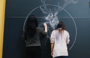 Priscilla and Jessica draw use to chalk to draw a stag.