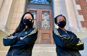 Jeana Choi (left) and Koumani Ntowe (right) in black adidas sweatshirts with gold strips and black facemasks posing with their arms crossed