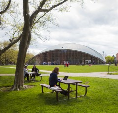 Student sitting at picnic table on Kresge Oval