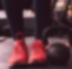 Blurred picture with red sneakers and kettlebells