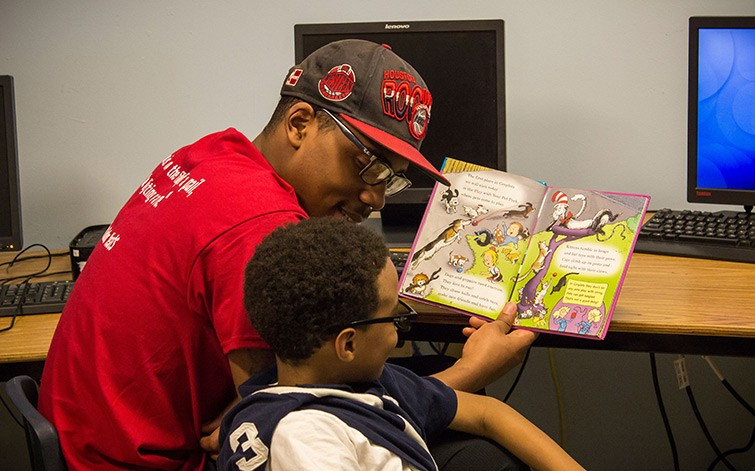 Makai helps a child reading.